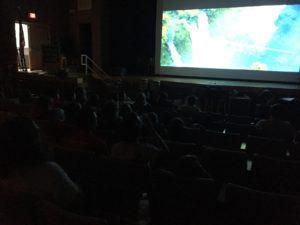 Students watch a movie in a dark auditorium