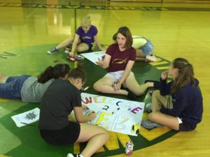 Students participating in the WEB (Where Everyone Belongs) training and orientation make posters in the gym.