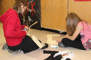 Students use paper and glue to create a ghost character