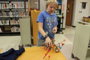 A student builds a vehicle with K'NEX