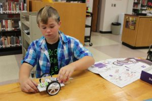 A boy makes a vehicle using K'NEX