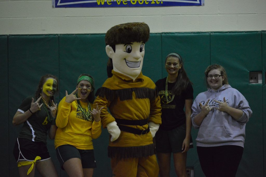 Students post with the school mascot in a gym