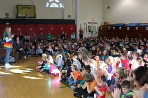 Elementary students listneing in gym during assembly