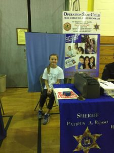 A female student sits at the sheriff's table
