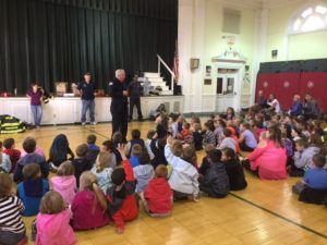 Students listen to a firefighter speak during assembly