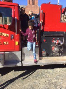 student climbs off a firetruck