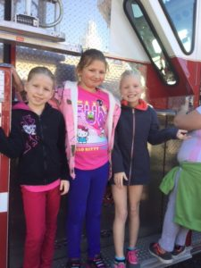 Smiling students standing on back of firetruck