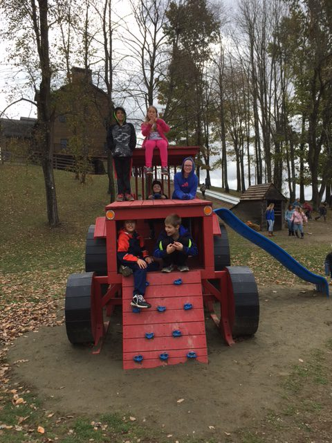 Students play on playground equipment that looks like a tractor
