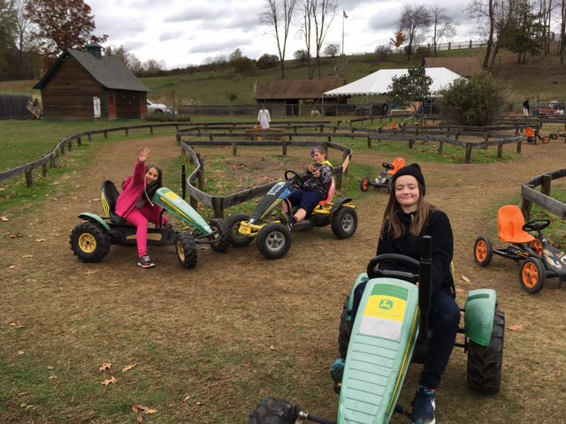 Students play on playground equipment that look like tractors