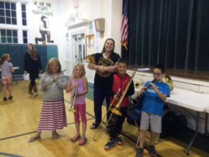 students with Ms. Keem holding their newly chosen instruments