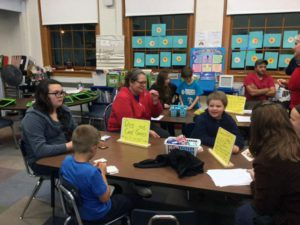 families & students working on problems sitting in a classroom during math night