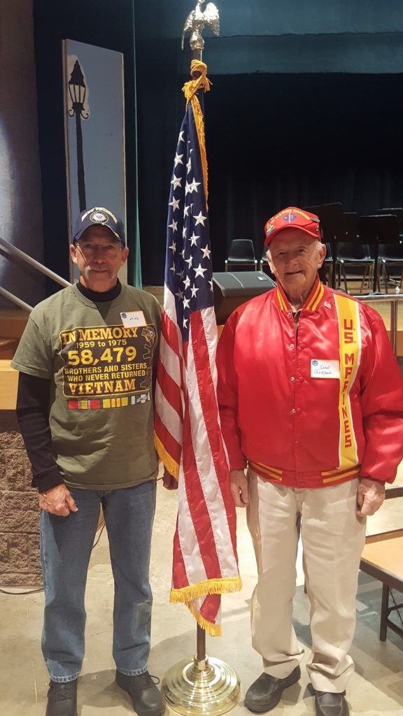 Local veterans stand next to an American flag in the auditorium
