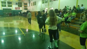 Students stand in a gymnasium