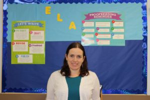 Ms. Hart stands in front of a blue bulletin board