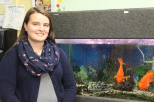 A science teacher stands in front of the fish tank in her classroom