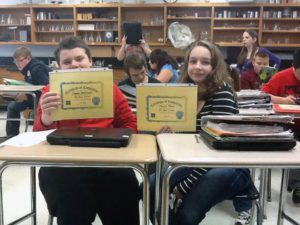 Two students sitting at desks holding certificates