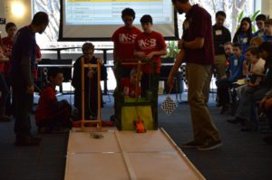 Students race gravity-driven cars on a floor track