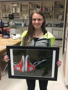 Girl holds framed artwork