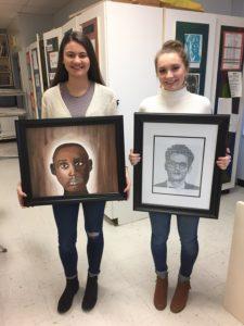 Two girls hold their framed artwork
