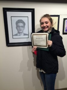 Student holding certificate at art show