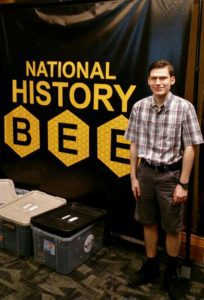 Andrew in front of National History Bee sign