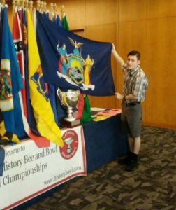 Andrew holds the flag of New York State