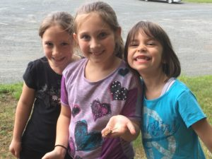 Three students hold butterflies they releasaed
