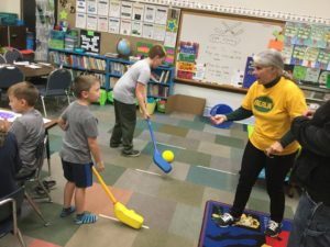 Students hitting a ball during sports literacy night