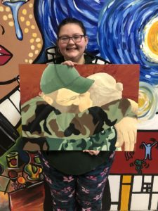 "Savanna Garcia (Grade 12) with her oil painting titled ""Strong Connection,"""