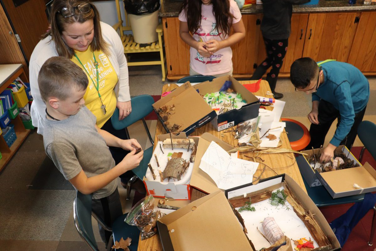 photo of students and a teacher around a table building dioramas